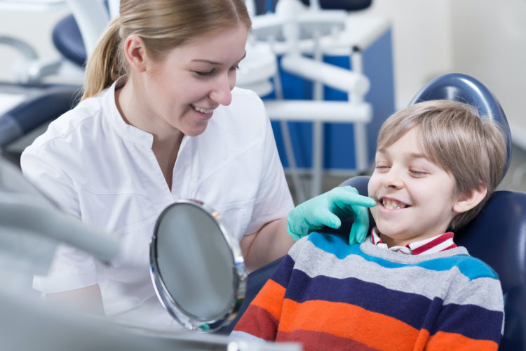 Schoolboy in a dentist chair smiling to a mirror held by a dental assistant sitting next to him